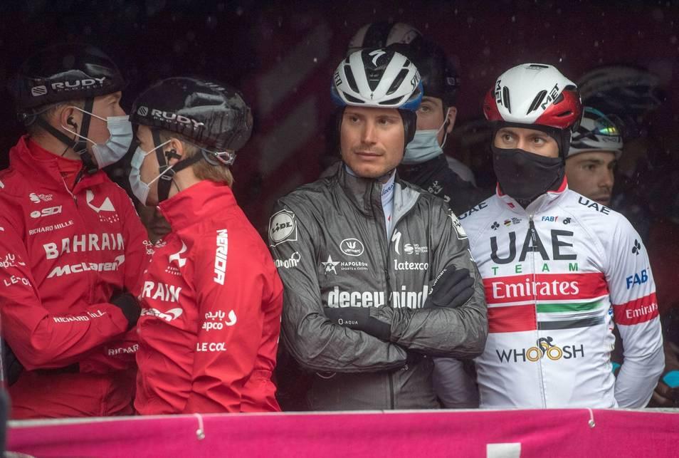 Los ciclistas del Giro esperando bajo la lluvia la decisión final de la etapa 19 del Giro d'Italia 2020